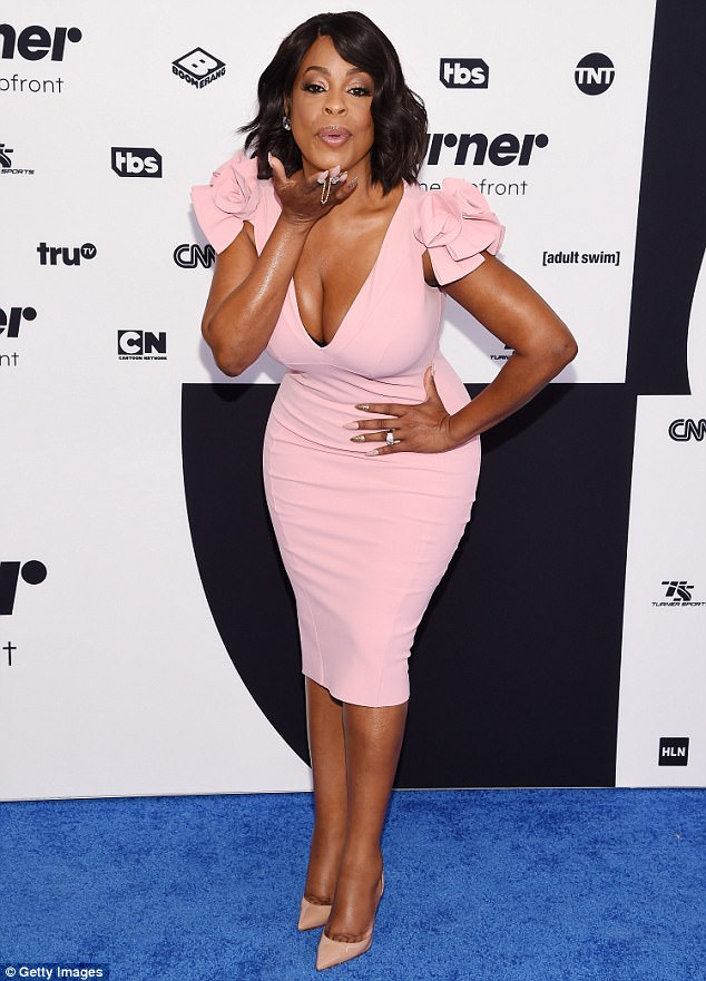 Kisses: Claws actress Niecy Nash flaunted her curves in a skintight pink dress with floral detailing along her shoulders
