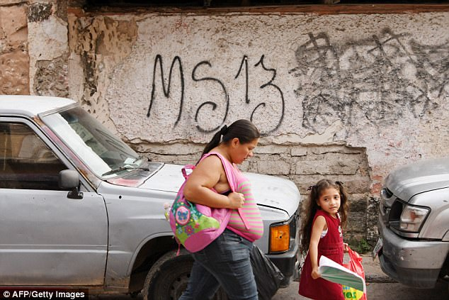 Local residents pass by graffiti in the MS-13-controlled El Bosque neighborhood in Tegucigalpa