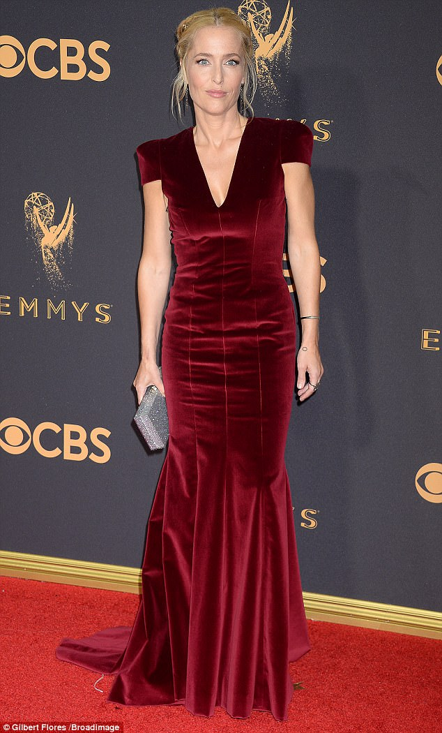 Burgundy beauty: Gillian Anderson, 49, stuns in a russet velvet gown with delicate lacing along the back as she walks the Emmys red carpet