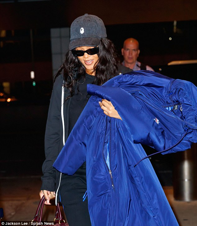 Covering up: The singing queen added a further shade of secrecy to her airport attire with a denim baseball cap and dark sunglasses which shielded her eyes from many