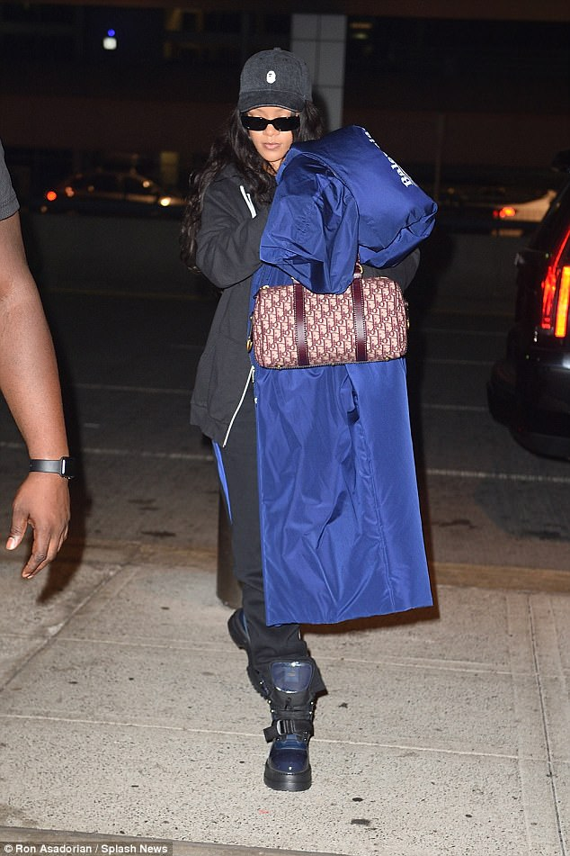 Going incognito: The 29-year-old singer looked worlds away from her trademark sexy attire as she covered her famous face with a huge electric blue padded jacket