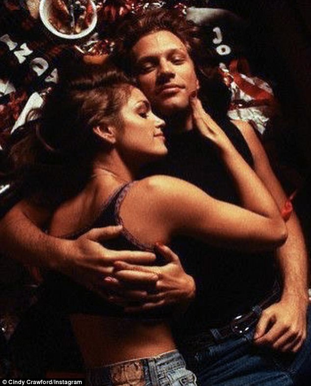 Not lonely this Christmas: The supermodel, 45,  cuddled the band's frontman Jon Bon Jovi, 55, while lying on top of him in one of the snaps