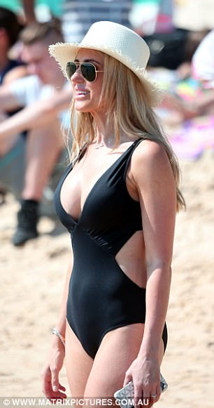Couldn't be happier: Sporting a designer black cut-out one-piece, the 37-year-old was all smiles as she flaunted her new assets