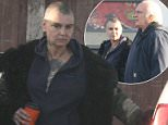Sinead O'Connor walks between two vehicles carrying an orange and black takeaway coffee cup and a green plastic bag