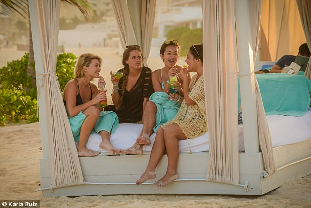Having a chat: Soon after, her and group of friends took a dip in the ocean and then headed to their own private cabana