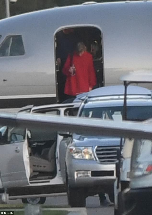 Seasonal: The Grammy-winner was decked out in Christmas colors as she got off the aircraft
