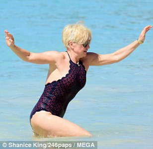 Uh oh: Emma lost her footing as she walked towards the surf