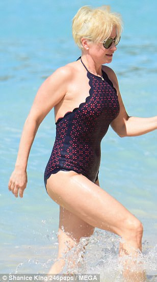 Water about that: Her beach attire featured a daring low-back which she flaunted as she stepped in and out of the idyllic waters