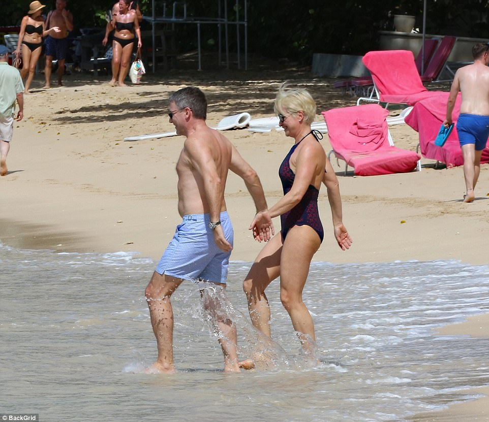 Happy: Graham searched for Emma's hand as they stepped into the sea