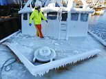 With temperatures in the single digits, Ray Levesque, mate of the crab/lobster boat Bradbill, makes his way across the deck covered in ice to tie off, after arriving in New Bedford, Massachusetts harbor on Thursday from a one day fishing voyage