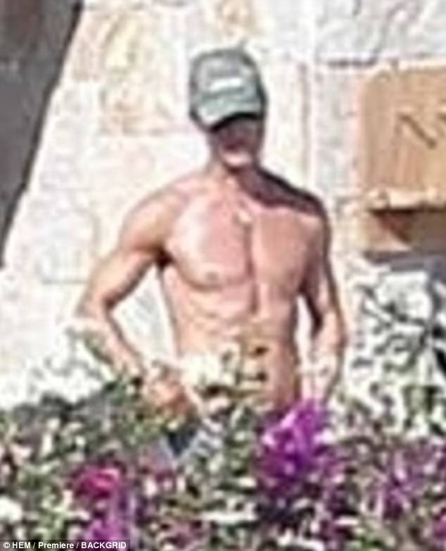 In shape: Her shirtless husband was showing off his muscular physique at the poolside