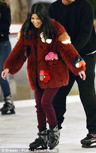 Fashionista: As always, Kourtney kept things stylish for the outing, bundling up in a rust colored coat with shapes embroidered on the outside