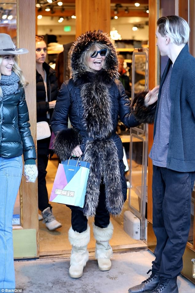Good spirits: Goldie sported a pair of matching furry snowboots as she headed into the shops