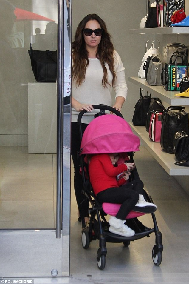 Fashionable:Sophia, meanwhile, looked typically stylish in a festive red jumper and fur-trim high trainers as she kicked back in her pink buggy