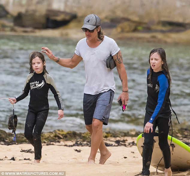 Family fun day! Keith was pictured walking with his two children alongside the water's edge, as they dragged their surfboards along the sand