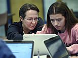 In this, Dec. 20, 2017 photo, Jennifer Rocca, left, a teacher librarian at Brookfield, Conn., High School, left, works with Ariana Mamudi, 14, a freshman in her Digital Student class. The required class teaches media literacy skills and has the students scrutinize sources for their on-line information. (AP Photo/Stephen Dunn)