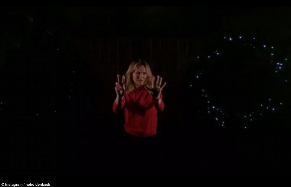 Smouldering: On the seventh day of Christmas Amanda merely stood holding up seven fingers while promoting the wreaths erected outside her house and posing provocatively