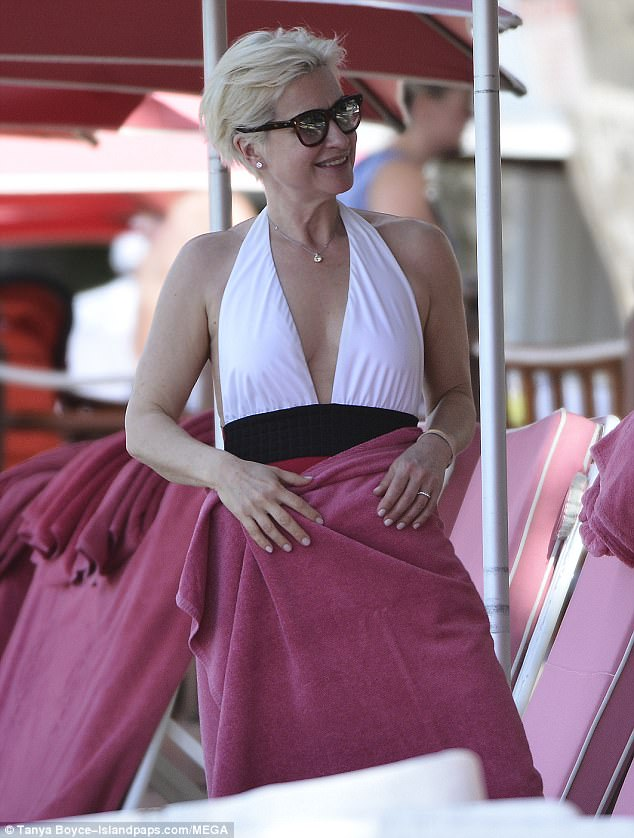 Stunning: Her plunging swimsuit was backless but she kept a towel on to dry off