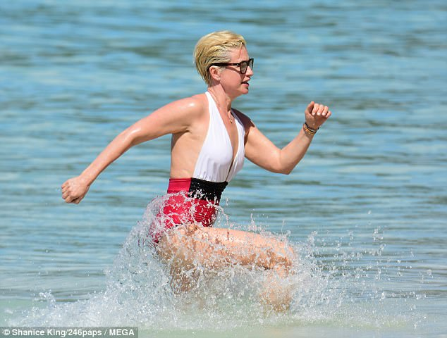 Flawless: Emma rocked the red, white and black swimsuit, with the deep v-neck showcasing her ample cleavage