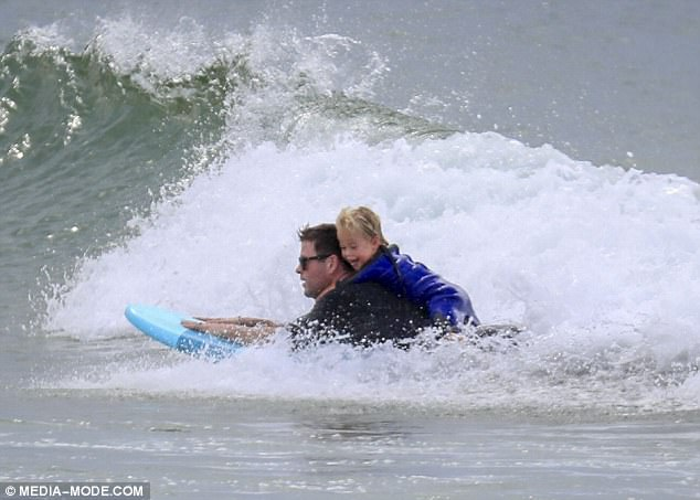Thrill-seekers!Clinging to his famous father's back, the little one looked delighted as he surfed the swells in style