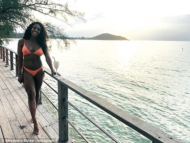 Coy: Alexandra  looked sensational in an orange triangle bikini, while hiding her ring finger behind a white cocktail glass in a scenic snap