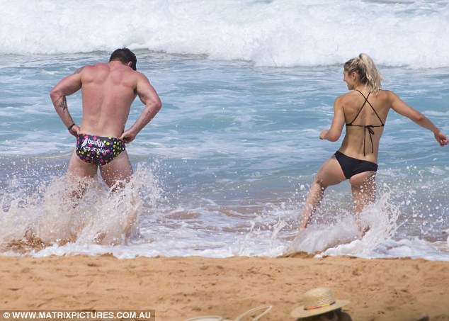 The pair were spotted running up and down nearby hills before cooling off in the surf