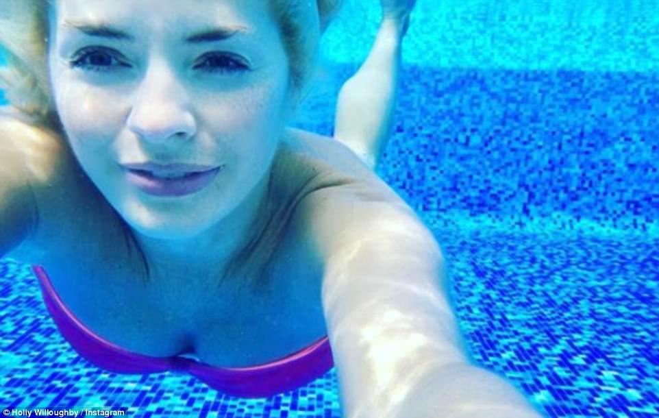 Sun-seeker: Holly revealed she had jetted overseas to see in 2018 on New Year's Eve, as she shared a cool underwater shot of her posing in the pool while clad in a colourful bandeau bikini