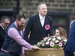 Malcolm Willsher (right), fastened a pink gerbera to his suit as he took the coffin of his wife Jodie in to Christ Church in Skipton