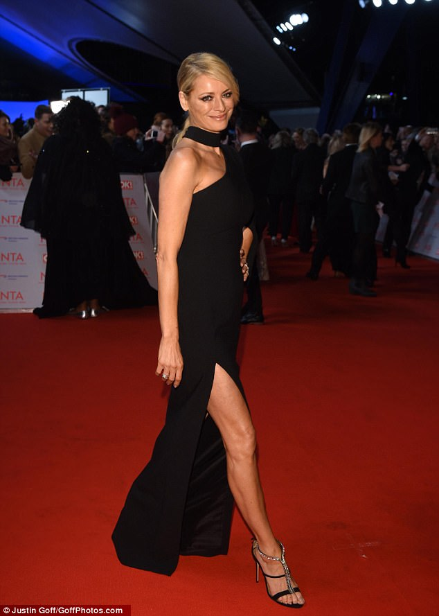 Beaming: Her form-fitting garb was sure to set pulses racing as a dangerously high thigh slit gave a glimpse at her leggy frame as she sauntered down the red carpet