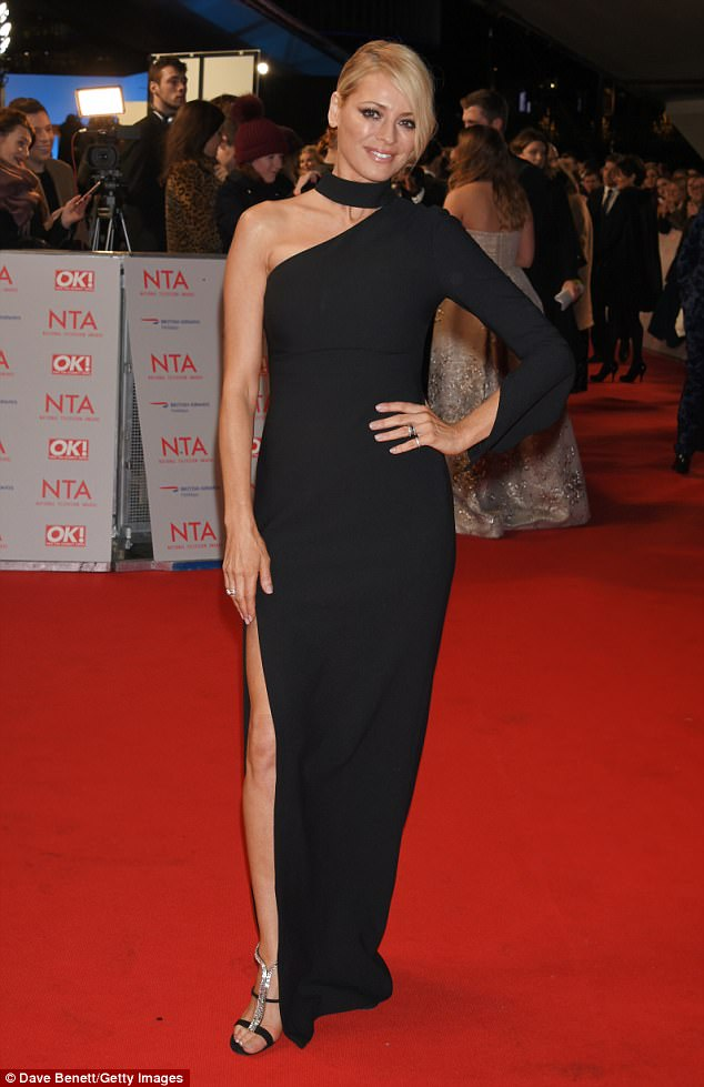 Leggy style: Tess Daly, 48, flaunts her impeccable pins in a shoulder-baring black gown with ultra high thigh-high slit as she poses up a storm at the 2018 National Television Awards red carpet