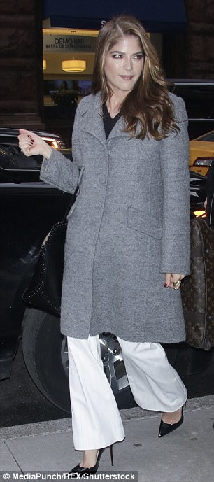 On trend: Earlier, she had arrived at the venue wearing a gray winter overcoat with wide lapels and angled pockets and in black pointed toe stiletto heels