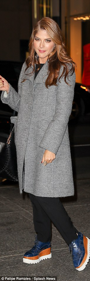 All smiles: She grinned as she posed in her sleek coat