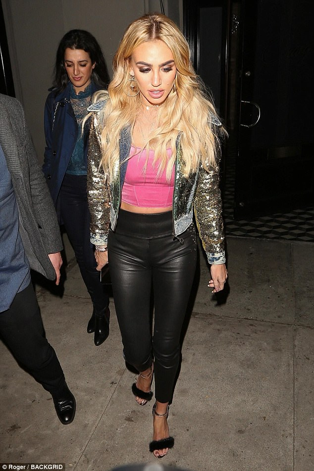 Chic: The socialite looked nothing short of glamorous, as she flaunted her physique in a pair of skin-tight leather trousers and a gold sequinned denim jacket