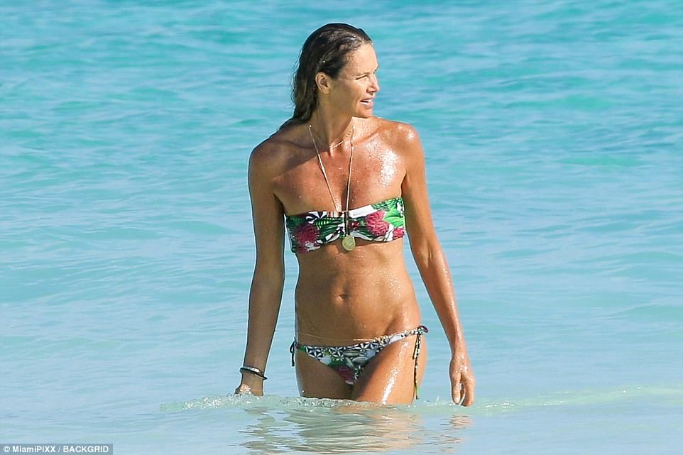 Flower power: The model, 53, showed off her incredible abs in a brightly-colored floral bandeau bikini as she soaked up the sun on her festive break