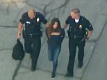Two 15-year-old students were shot inside a Los Angeles school on Thursday, and a female suspect was seen being taken from the scene in handcuffs