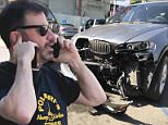 Jimmy Kimmel was involved in a car accident on Sunset Strip in Los Angeles Thursday morning. Kimmel is seen on the left talking on his cell phone while the driver of the other vehicle involved in the crash stands a few feet away from him (second from right)