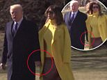 First Lady Melania appears to be hiding her hand beneath her coat while standing next toPresident Trump on Monday