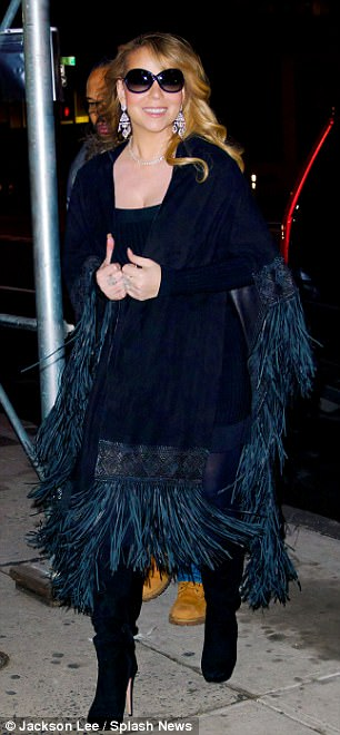 Ostentatious outwear: The 48-year-old mother-of-two paired her cape with yet another cleavage-boosting LBD, black tights, and matching thigh-high suede boots
