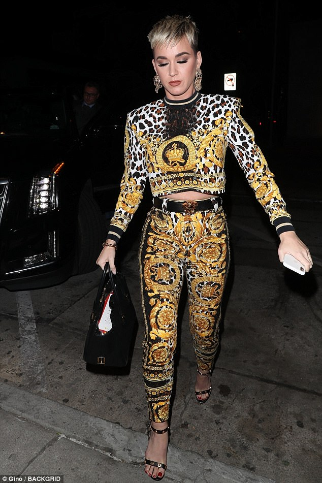 Coordinated look: Katy stepped out in a pair of sandal heels embellished with metallic studs and sported red color on her toenails. She carried a large black leather tote