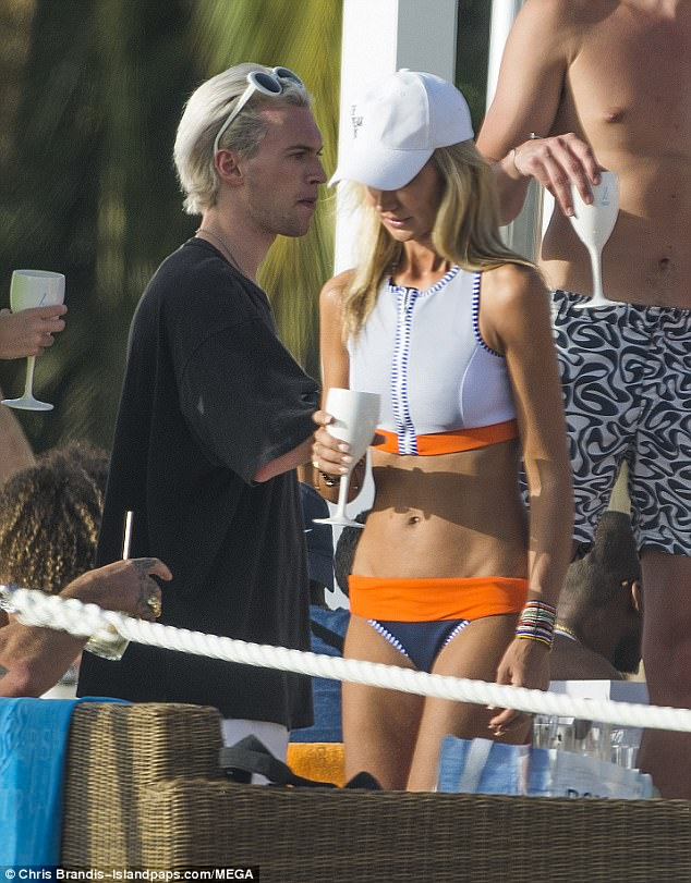 Turning heads:The blonde beauty looked every inch the beach babe in her chic swimwear, which featured shades of navy, orange and ivory