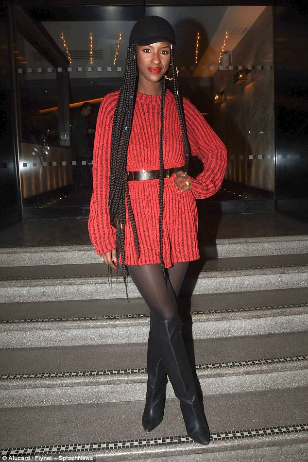 Leggy lady: Sarah Mulindwa showcased her enviable legs in a thigh-skimming scarlet knitted dress, teamed with knee-high boots