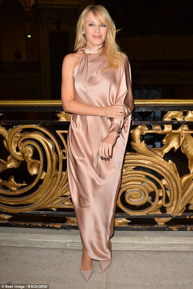 Say cheese: The singer, 49, looked truly stunning in a slinky pink dress of pastel pink silk as she effortlessly posed in front of a gold balcony inside the event