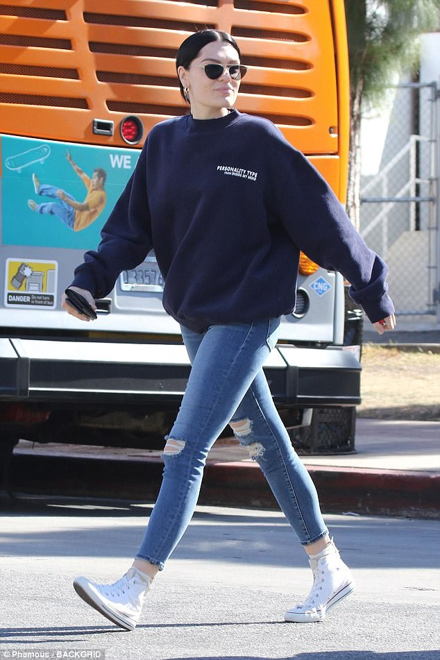Warm: Her long legs were on display in a pair of tight distressed denim pants with the hems rolled up above her ankles