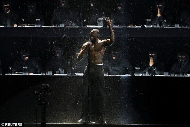 Powerful: The star proceeded to remove his jumper as he performed with a heavy gush of artificial rain