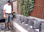 In a satisfyingly good video, a bricklayer (pictured) used a nifty domino method to make dozens of stone slabs fall into place at once