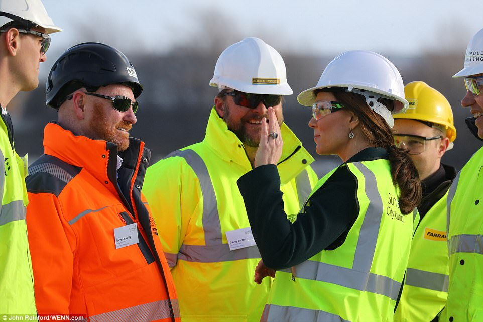 Seemingly pleased with her handy work the Duchess of Cambrifdge offered construction workers a high five on the bridge