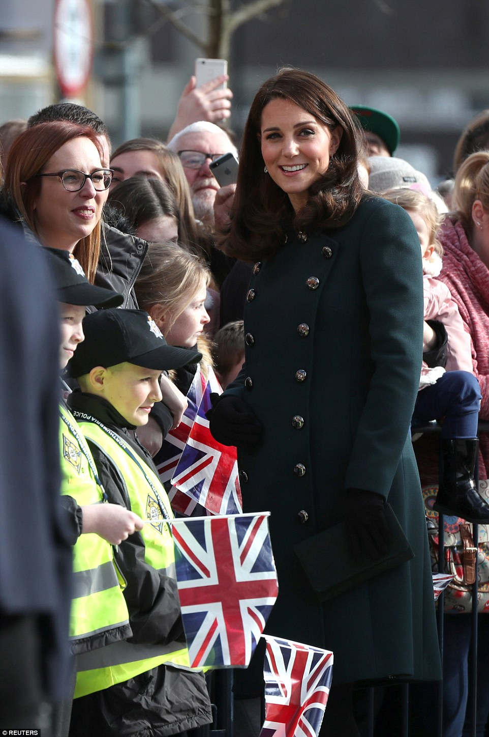 The Duchess of Cambridge showcased her blossoming baby bump in a forest green Dolce & Gabbana coat during a visit to Sunderland on Wednesday