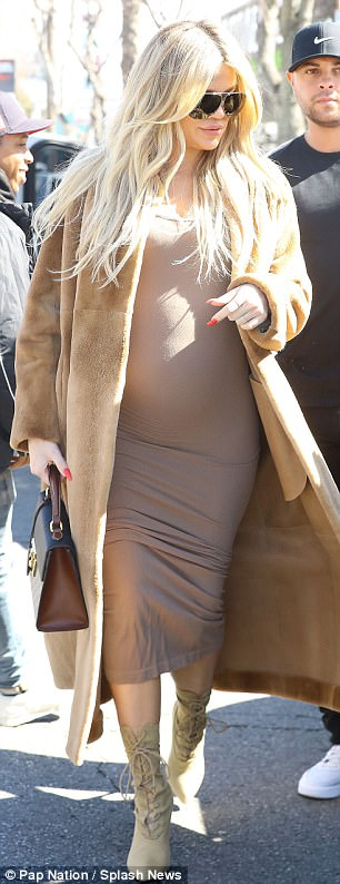 Casual chic: Over the tight-fitting number she wore a long brown fur duster coat