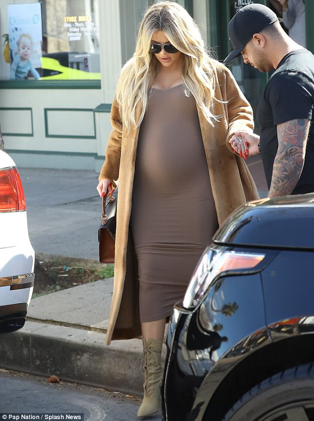 Strutting her stuff: Her growing belly was on full display in a clinging dark beige Ronny Kobo midi dress which she paired along with matching military lace-up boot inspired heels