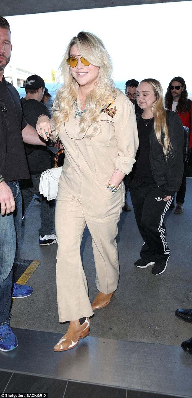 Simply stunning:Wearing her voluminous blonde hair in a side-swept style with flowing waves, Kesha looked radiant from head-to-toe as she made her way into the transport hub